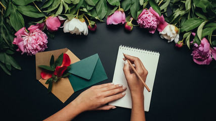Woman writing a letter. Female hands writing on white paper. Beautiful white and pink peonies flowers on the black background. Table top view. Flat lay