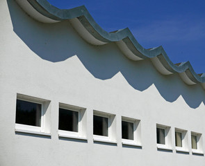 Detail of a white facade and a wavy roof