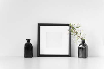 Black square frame mockup with spring cherry branch. Mock up for your photo, design or text.