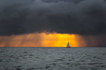 Boat sailing into the storm sunrise