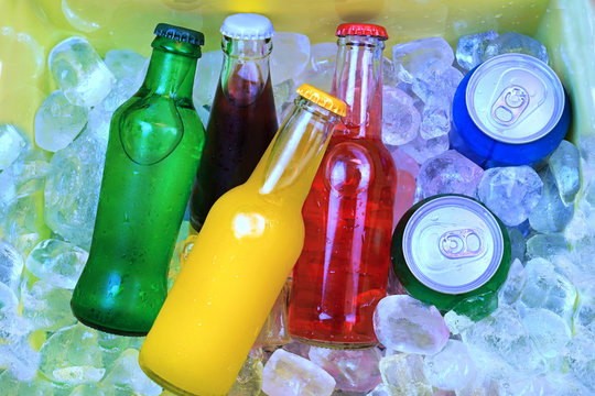 Colorful cold soda drinks, filled ice cubes in a cool box