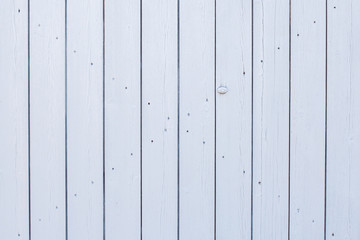 Wooden slats painted white. Wooden door gate white. Boards nailed together. Parallel vertical lines of boards