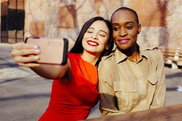 Portrait two friends taking selfie while sitting at a table in an urban park