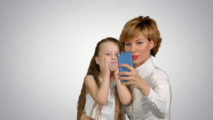 Cute family mother with child daughter taking selfie smart phone photo on white background
