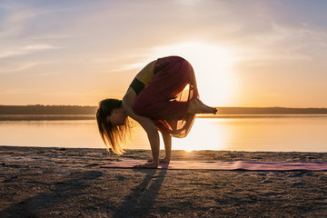 Silhouette woman on the beach at sunset doing yoga asana. Morning natural stretch warm-up training