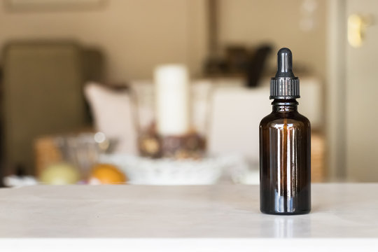 A medicine bottle with dropper over a home blur background.