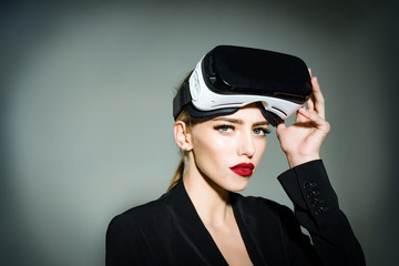 Beautiful woman in virtual reality headset. Sensual attractive girl with makeup in virtual reality goggles at head. Future. Future technology concept. Girl using VR headset.