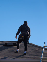 Worker inspecting a damaged roof
