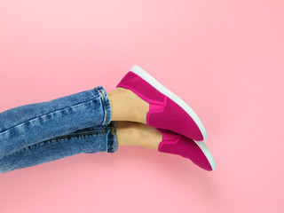 Legs of the girl in red sneakers and ripped jeans on the pink floor. The view from the top.