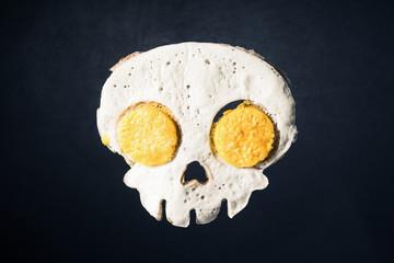 Foto op Canvas Gebakken Eieren Fried eggs in the skull shape against darken background