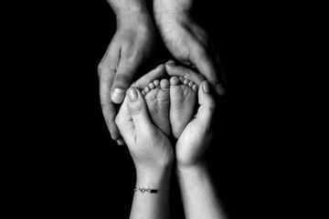 Hands hold newborn feet