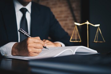 Close up lawyer businessman working or reading lawbook in office workplace for consultant lawyer...