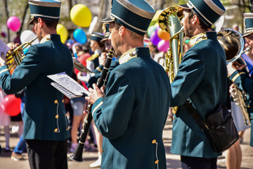 Performance of the brass band at the city festival. Musicians with french horn, trumpet, trumpet, saxophone, clarinet
