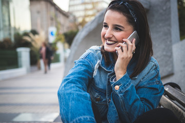 Urban cool young woman speaking on the phone in the city.