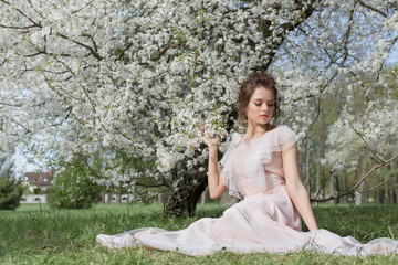 beautiful tender sweet girl in a pink dress with a hairdo near blossoming tree on a sunny spring day