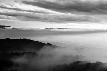 Umbria valley in autumn filled by mist, with emerging hills and