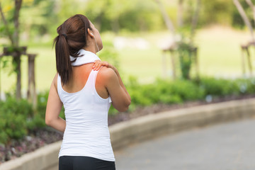 Neck pain during training. Athlete running woman runner with sport injury rubbing and touching upper back muscles outside after exercise workout in summer.