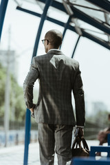 African american businessman wearing suit walking on train station