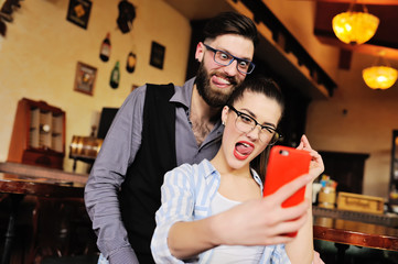 young couple - guy and girl posing and grimacing on the smartphone's camera, making selfie on the background of the bar.