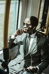 African american businessman wearing suit listening to music while taking train