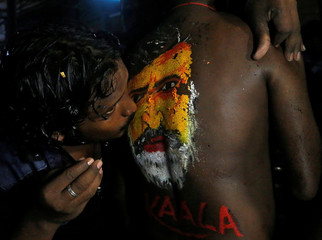 "A fan kisses an image of actor Rajinikanth painted on the body of another as they celebrate the release of his new movie ""Kaala"" in Mumbai"