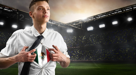 Mexico soccer or football supporter showing flag under his business shirt on stadium.
