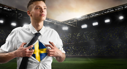 Sweden soccer or football supporter showing flag under his business shirt on stadium.
