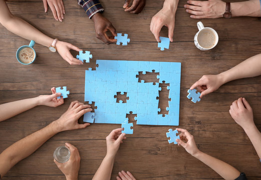 People with puzzle on wooden background, closeup of hands. Unity concept