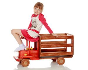 Little girl is playing with a wooden car.