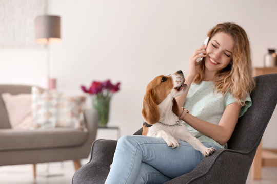 Young woman talking on phone while stroking her dog at home