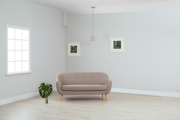 Living room interior with comfortable sofa near light wall