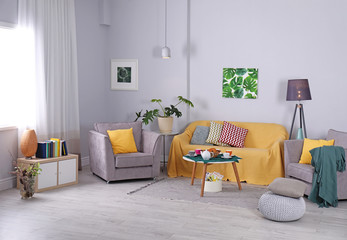 Elegant living room interior with cozy sofa and armchairs