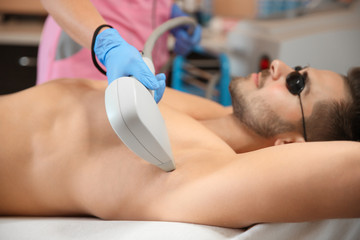 Young man undergoing laser epilation procedure in beauty salon
