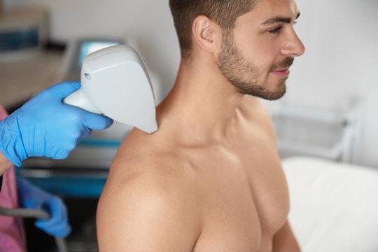 Young man undergoing laser epilation procedure in beauty salon