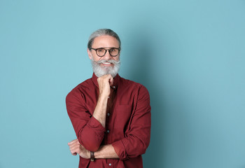 Portrait of handsome mature man on color background