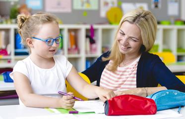 Lehrerin hilft Schülerin beim Lernen