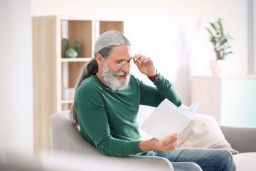 Handsome mature man reading book on sofa, indoors