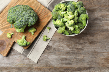 Flat lay composition with fresh green broccoli on wooden background