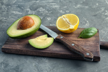 Wooden board with cut avocado, lemon and knife on grey background