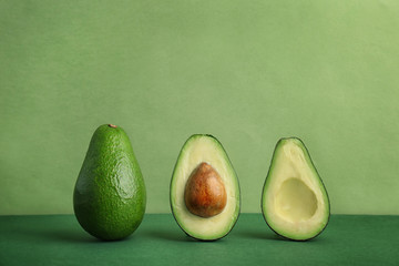 Composition with ripe avocados on color background