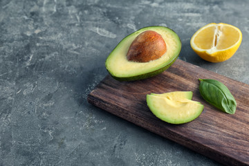 Wooden board with cut avocado and lemon on grey background