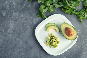 Flat lay composition with ripe avocado and mint on grey background