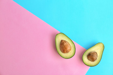 Halves of ripe avocados on color background, top view