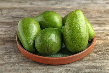 Plate with ripe avocados on wooden background