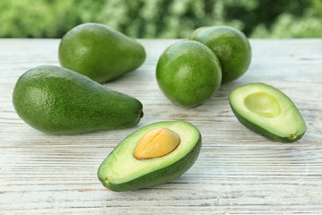 Ripe avocados on wooden table against blurred background
