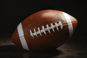 New American football ball on table against dark background