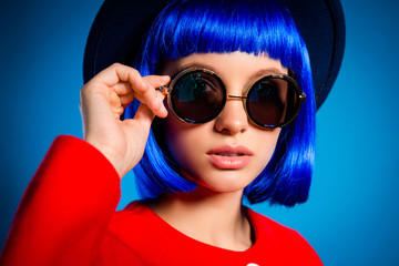 Close up cropped portrait of fashionable elegant girl in summer glasses holding eyelet with hand looking at camera isolated on blue background. Rest relax leisure weekend concept