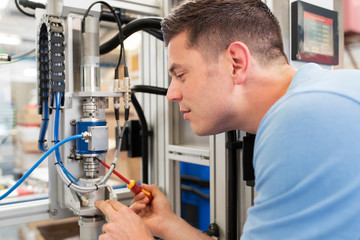 Male Engineer Working On Machine In Factory
