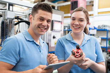 Portrait Of Engineer And Apprentice Examining Component In Factory