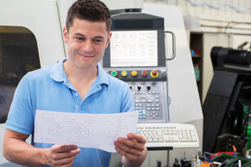 Male Engineer With Technical Drawing Operating CNC Machine In Factory